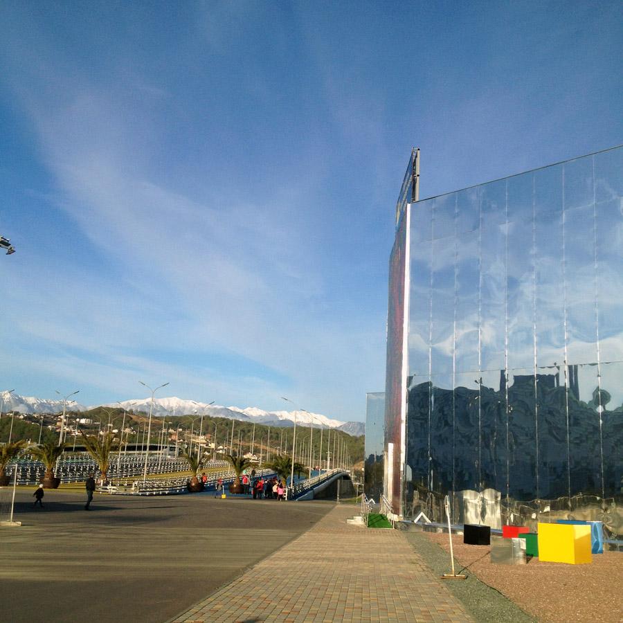 Зеркальное здание около пешеходного моста в Олимпийском парке
